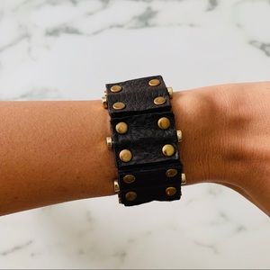 Brown leather bracelet with gold detail.